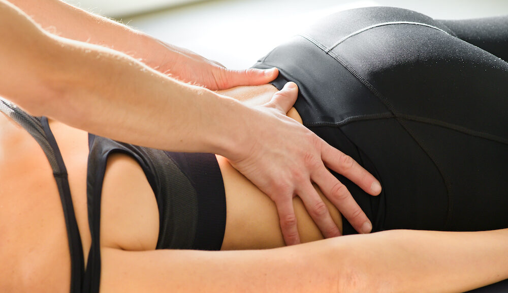 Osteopath performing sacral decompression osteopathy on a young woman manipulating her spine and lower back to realign and reposition the vertebrae