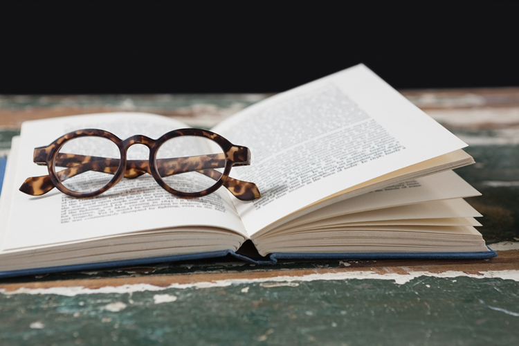 Close-up of spectacles on open book